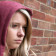 Sulky blonde teenage girl wearing a hoodie leaning against a wall, Billericay Essex UK